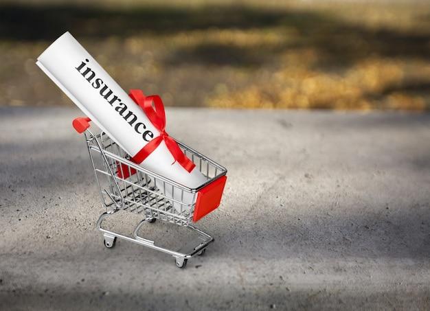 Papierbündel mit wortversicherung und band im spielzeug-einkaufswagen im hintergrund