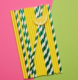 Papiercocktailröhrchen auf einem grünen rosa
