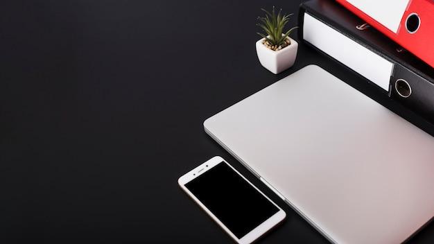 Papierdateien; topfpflanze; geschlossener laptop und smartphone auf schwarzem hintergrund