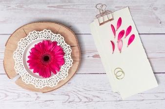 Papiere mit Blumenblättern und Ringen in der Nähe von Blumen auf Holz Runde