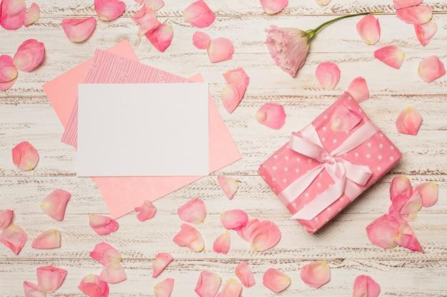 Papiere zwischen blütenblättern in der nähe der geschenkbox