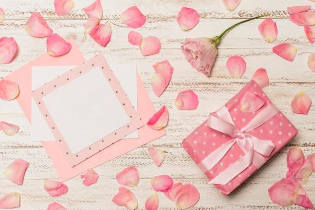 Papiere zwischen blütenblättern in der nähe von geschenkbox