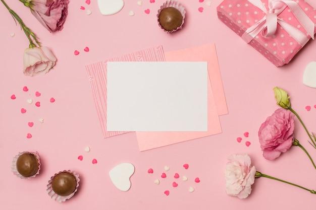 Papiere zwischen symbolen von herzen, süßigkeiten, geschenk und blumen
