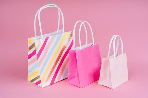 Papiereinkaufs- oder -geschenktüten auf rosa hintergrund mit kopienbadekurort. konzeptverkauf, einkauf, schwarzer freitag.