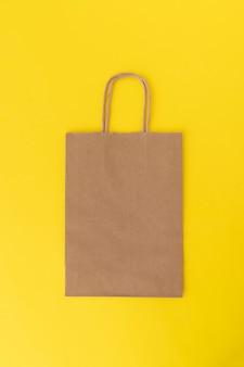 Papiereinkaufstasche auf gelbem hintergrund. speicherplatz kopieren. attrappe, lehrmodell, simulation. vertikaler rahmen