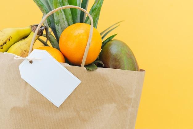 Papiereinkaufstasche gefüllt mit tropischen früchten und weißem etikett auf gelbem hintergrund. attrappe, lehrmodell, simulation. platz kopieren.