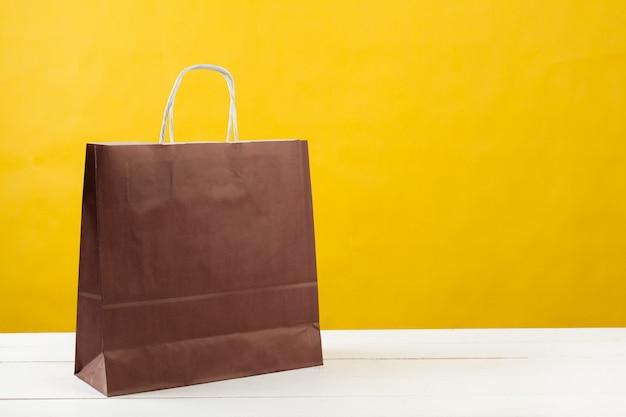 Papiereinkaufstaschen auf hellem gelbem hintergrund