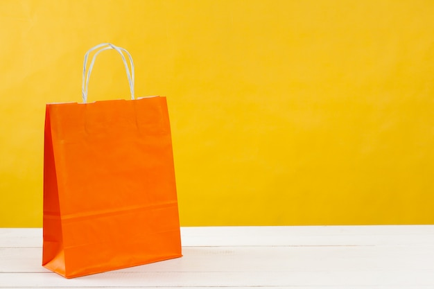 Papiereinkaufstaschen auf hellgelbem hintergrund