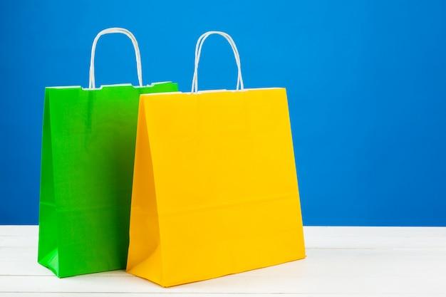 Papiereinkaufstaschen mit kopienraum auf blauem hintergrund
