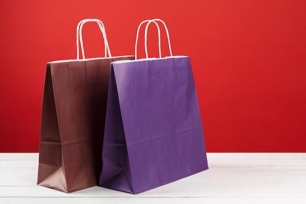 Papiereinkaufstaschen mit kopienraum auf rotem hintergrund