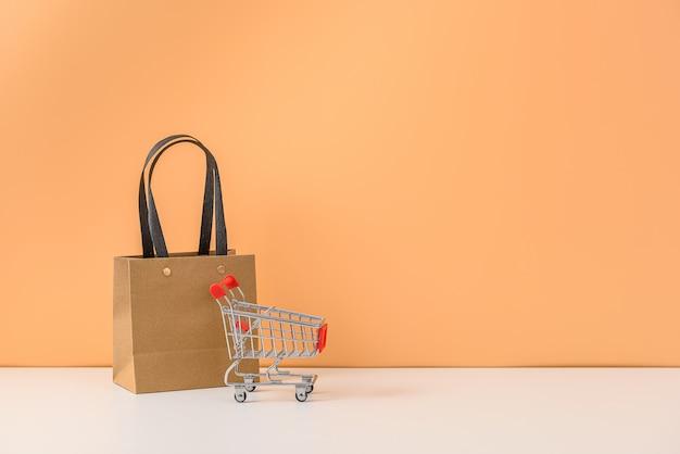 Papiereinkaufstaschen und einkaufswagen oder wagen auf weißem tisch und pastellorange