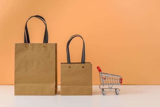 Papiereinkaufstaschen und einkaufswagen oder wagen auf weißem tisch und pastellorangeem hintergrund
