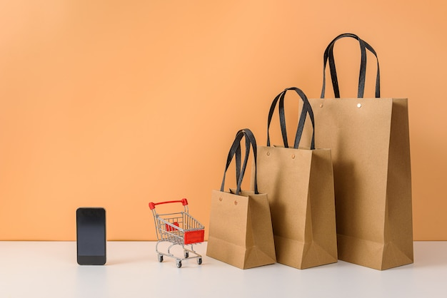 Papiereinkaufstaschen und warenkorb oder laufkatze mit smartphone auf weißer tabelle und orange pastellwand