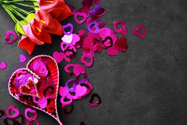Papierelemente in form von herzen auf dunklem steinhintergrund. liebe und valentinstag konzept. geburtstagsgrußkartendesign.