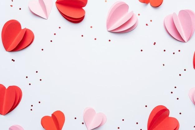 Papierelemente in form von herzen auf weißem hintergrund. symbole der liebe für glückliche frauen, mutter, valentinstag, geburtstag. draufsicht einer grußkarte. flach liegen