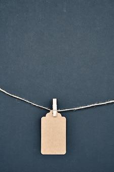 Papieretiketten werden mit wäscheklammern am seil auf schwarz befestigt.