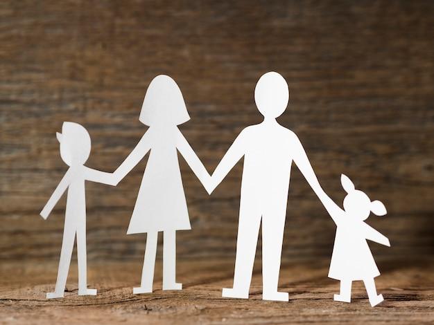 Papierfamilie auf hölzernem hintergrund