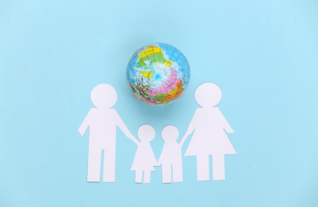 Papierfamilie zusammen mit globus auf blau. konzept der ökologie, bevölkerung, familie, tag der erde. welt unser haus