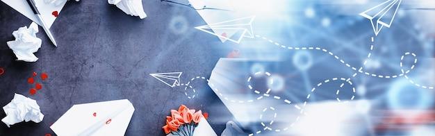 Papierflieger auf dem tisch. origami-modell auf dunklem hintergrund. konzept. kreative zeitverschwendung.