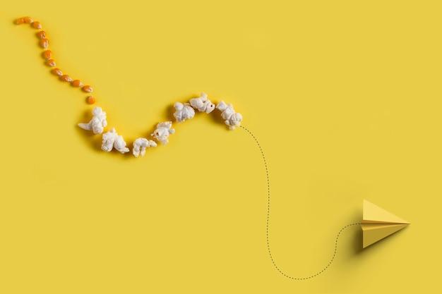 Papierflieger fliegen mit einer reihe von maiskörnern und popcorn auf gelbem grund. konzept des wachstums, unternehmertum.