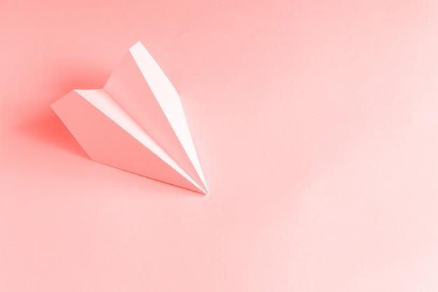 Papierflugzeug auf einem korallenhintergrund. trendiges farbkonzept 2019