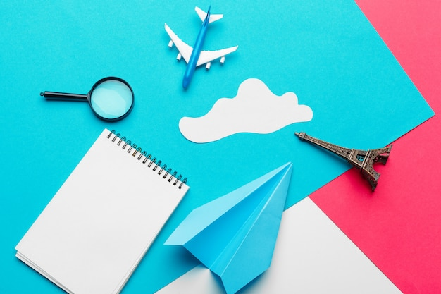 Papierflugzeug auf einer blauen farbe mit wolken