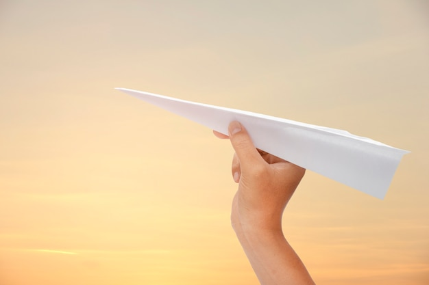 Papierflugzeug in der hand auf dem himmel
