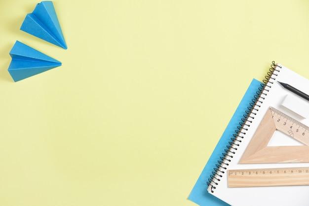 Papierflugzeug mit büromaterialien auf gelbem hintergrund