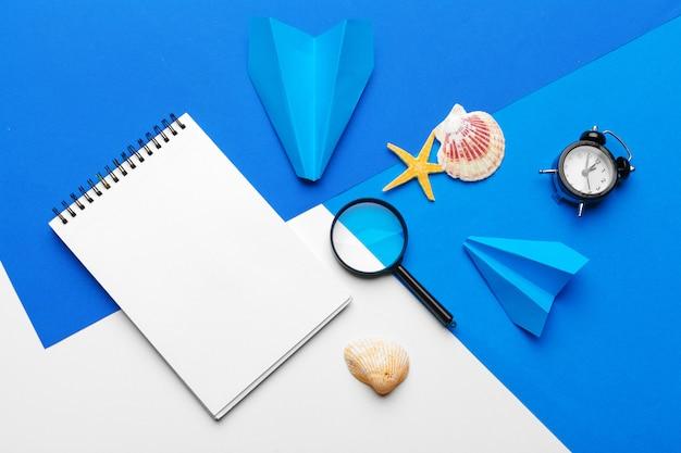 Papierflugzeug mit bürozubehör auf blau