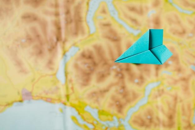 Papierflugzeug über kartenhintergrund