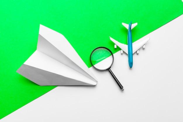 Papierflugzeuge, lupe und flugzeugspielzeug