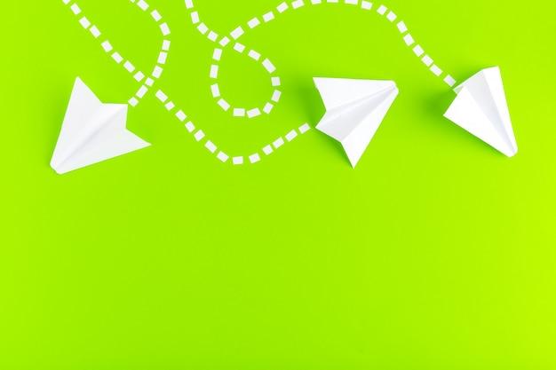 Papierflugzeuge verbunden mit gepunkteten linien auf grünem hintergrund. geschäftskonzept