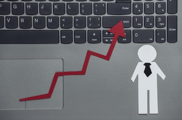 Papiergeschäftsmann und wachstumspfeil auf laptoptastatur. symbol für finanziellen und sozialen erfolg, treppe zum fortschritt