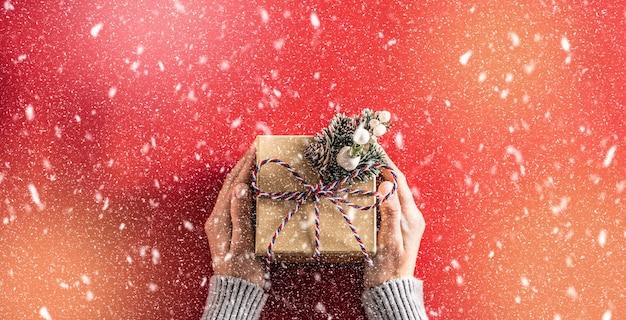 Papiergeschenkbox mit schleife in den händen der frau auf rotem hintergrund in abstrakten schneefällen.