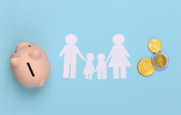 Papierglückliche familie zusammen mit sparschwein und münzen auf blau. familienbudget
