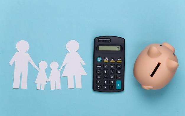 Papierglückliche familie zusammen mit sparschwein und taschenrechner auf blau. familienbudget