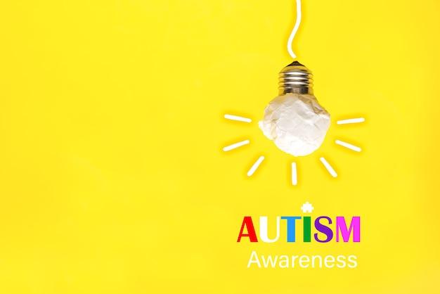Papierglühbirne auf gelbem hintergrund, welt-autismus-bewusstseinstag
