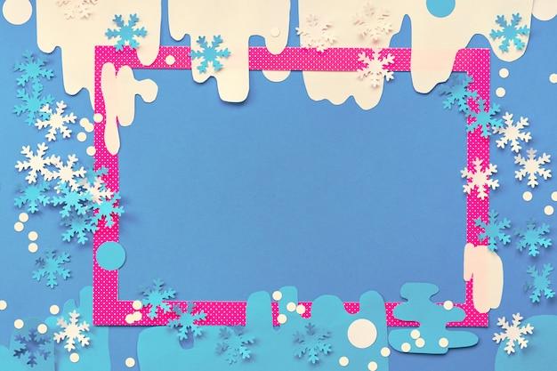 Papierhandwerk, draufsicht mit kopierraum. rosa oder magentafarbener rahmen mit papierschnee und verschiedenen schneeflocken. kreativer weihnachts- oder neujahrspapierhintergrund in blau, rosa und weiß.