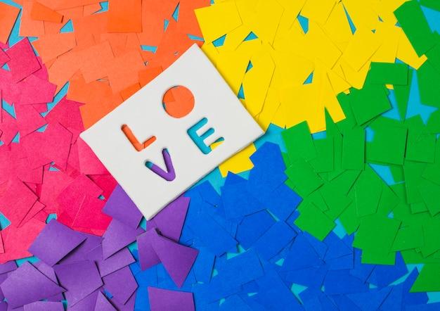 Papierhaufen in hellen lgbt-farben und liebeswort auf tablette