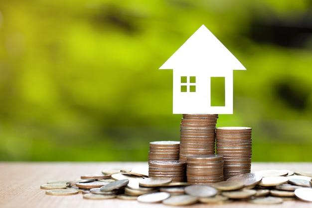 Papierhaus auf münzenstapel zum sparen, um ein haus zu kaufen.
