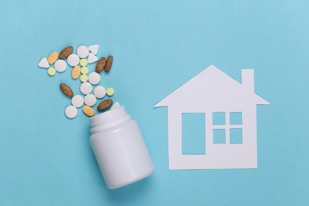 Papierhaus, flaschenpillen auf blau, krankenversicherungskonzept