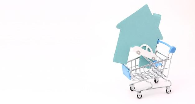 Papierhaus und papierauto im einkaufswagen