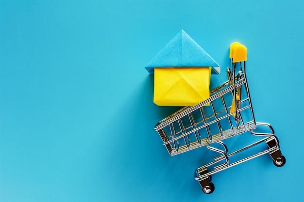 Papierhausmodell im minieinkaufswagen oder laufkatze auf blauem hintergrund