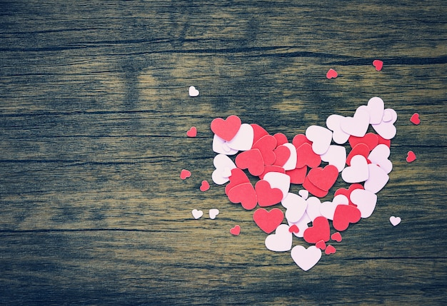 Papierherz am hölzernen rosa und roten herzen valentinsgrußtag für klassisches holz der liebhaber-tonweinlese