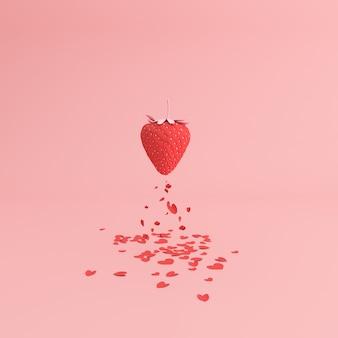 Papierherz, das von der roten erdbeere, valentinsgrußkonzept fällt.