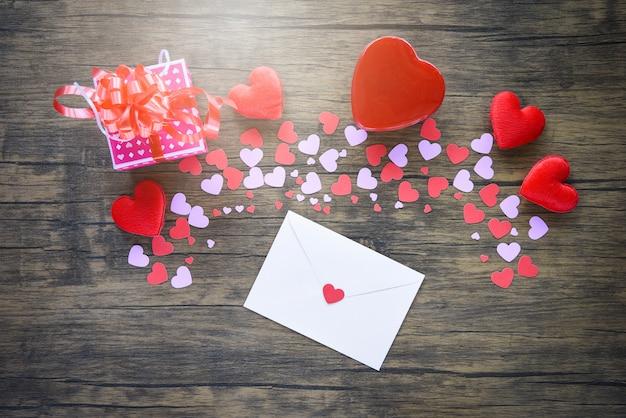 Papierherz und geschenkbox auf hölzernem rotem herzen valentinsgrußtagesbrief einladungskarte für liebhaber