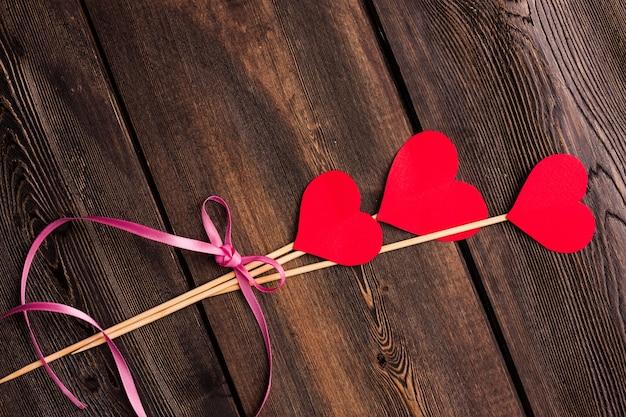 Papierherzen auf einer hölzernen hintergrundpostkartenbeschaffenheit valentinstag