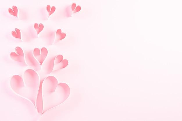 Papierherzen auf rosa pastellpapier
