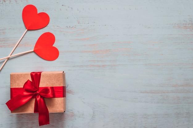Papierherzen auf stöcken und ein handwerksgeschenk mit rotem band auf einem hell gemalten hölzernen hintergrund. seitenansicht von oben, flach gelegt. valentinstag konzept. copyspace.