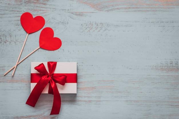 Papierherzen auf stöcken und ein weißes geschenk mit rotem band auf einem hellen gemalten hölzernen hintergrund. seitenansicht von oben, flach gelegt. valentinstag konzept. copyspace.
